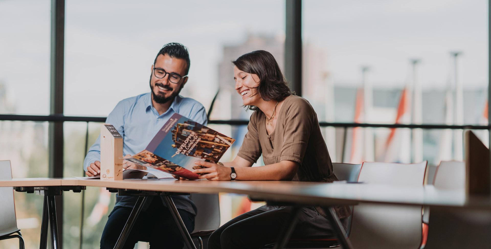 Une femme et un homme qui lisent une brochure