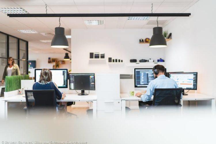 deux personnes travaillent sur des ordinateurs