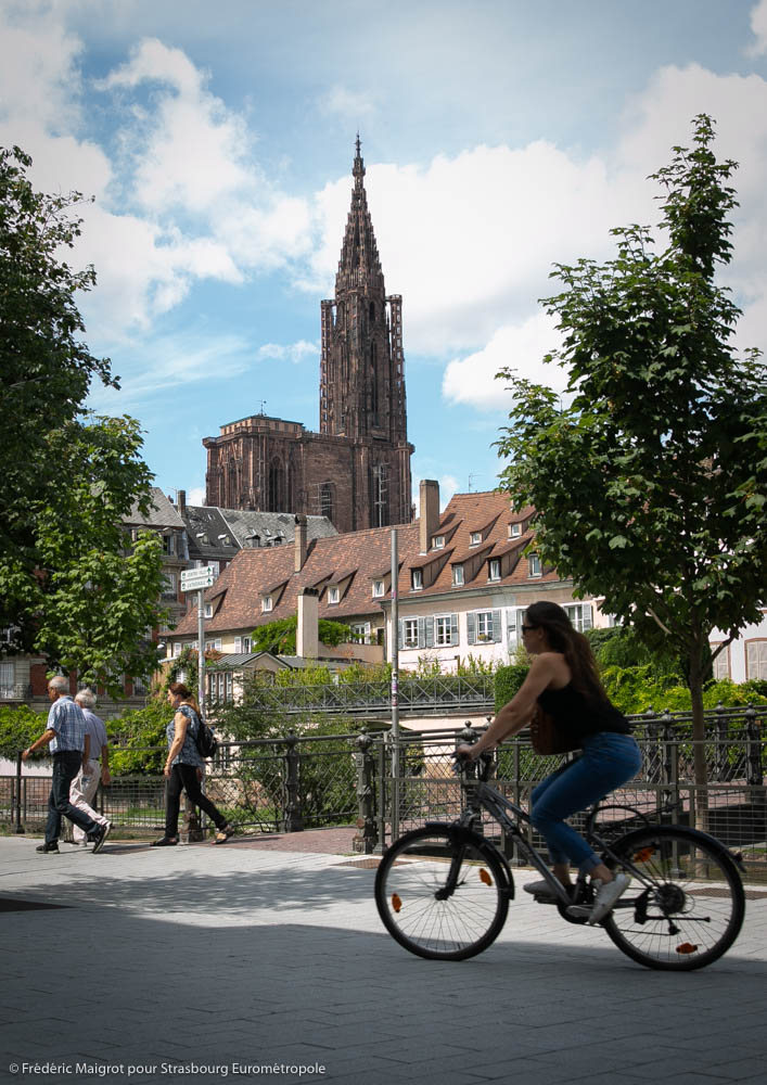 une femme roule à vélo sur les Quais des Bateliers de Strasbourg en vélo