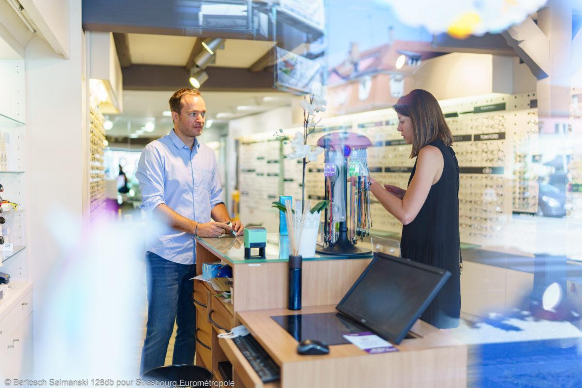 Un opticien et une cliente qui discutent dans le magasin