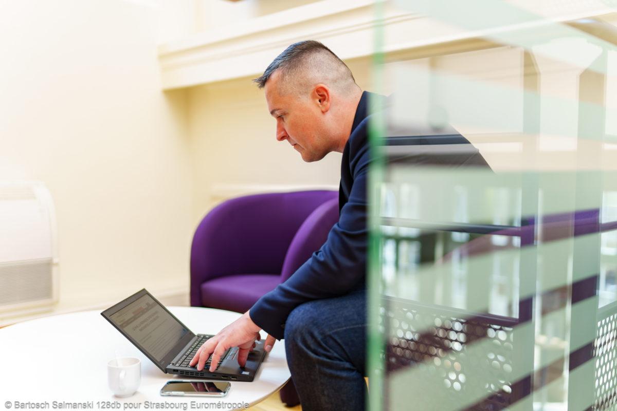 Un homme travaille sur son ordinateur dans une salle de repos