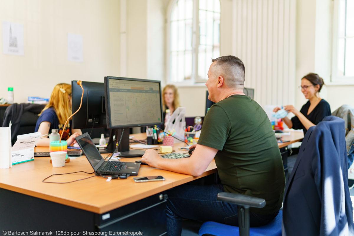 Plusieurs personnes se trouvent dans un bureau en train de travailler sur leurs ordinateurs
