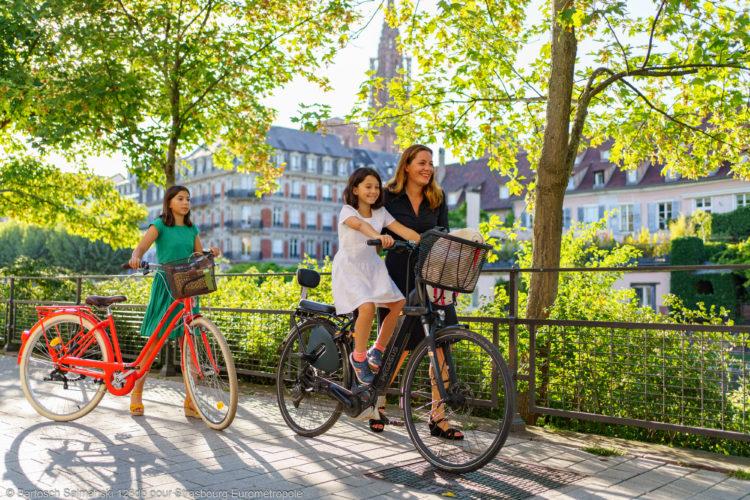 Une femme qui fait du vélo avec ses deux filles sur les quais de Strasbourg