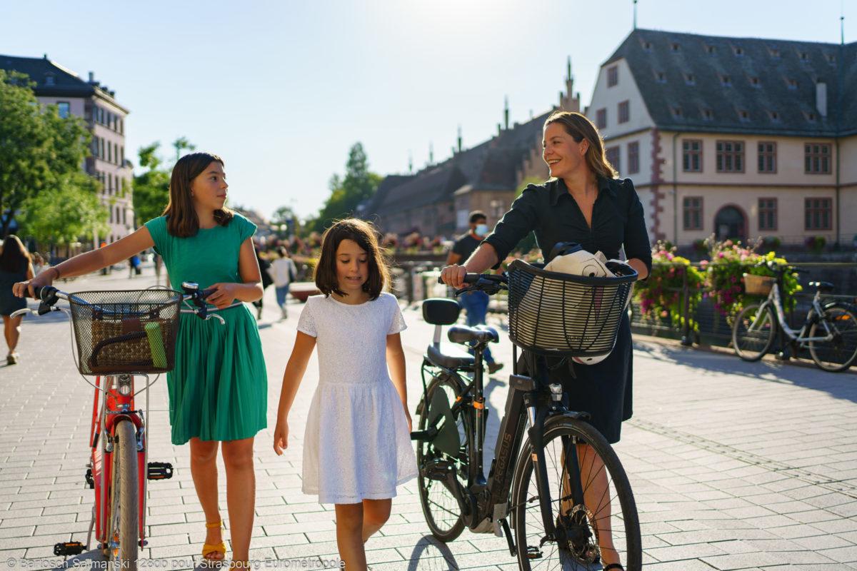 Une femme et ses deux filles se promènent sur les quais des Bateliers avec leurs vélos